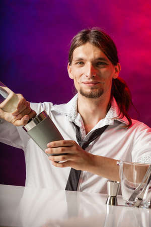 bartending: Alcohol liquor entertainment relax bartending concept. Barman fills shot glass. Young male bartender makes a drink. Stock Photo