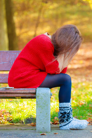 negative emotion: Loneliness negative emotion concept. Young sad stressed woman sitting in autumnal park. Stock Photo