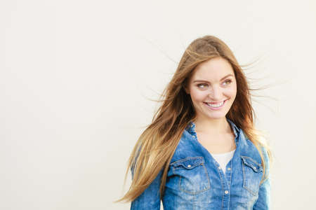 coiffure: Young woman with waving hairs. Girl wearing jeans jacket smiling.  Fashion coiffure lifestyle leisure concept.
