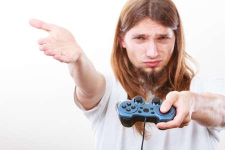 jugando videojuegos: concepto efectos de adicción. hombre deprimido infeliz joven con la almohadilla de joystick juegos de juego. Hombre adicto a la consola de videojuegos.