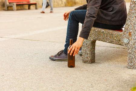 alcoholismo: Hombre deprimido con botella de vino sentado en el banco al aire libre. La gente abuso y problemas de alcoholismo.