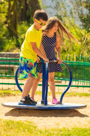 Joyful active childhood. Playful kids playing on playground. Children having fun in summer. Young tourists spending actively time. Stock Photo