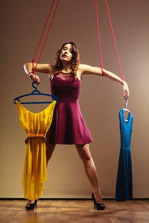 compras compulsivas: Shopaholic concepto de adicción de la moda. Adicto a la mujer de las compras, chica marioneta con ropa en cadena, la compra de trastorno.