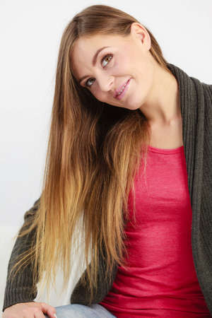 coiffure: Young woman with long hairs. Smiling girl looking at her coiffure. Fashion beautyr leisure concept.