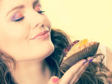 gir: Bakery sweet food indulging and people concept. Cute attractive woman closed eyes holds cake cupcake in hand smelling yellow background