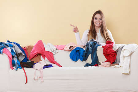 messy clothes: Happy woman behind sofa couch in messy living room pointing at empty blank copy space. Young girl surrounded by many stack of clothes. Disorder and mess at home.