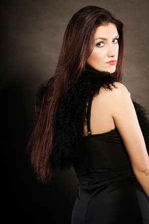 feather boa: Party celebration concept.  Magnificent long hair woman red lipstick wearing black evening dress feather boa on dark back view