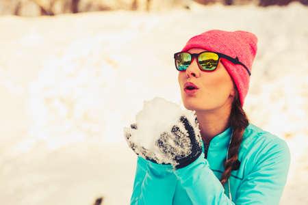 entertaiment: Girl having fun with snow. Winter park relax entertaiment fitness. Health nature fashion concept.