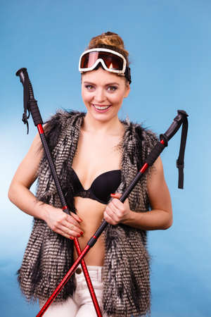 brassiere: Sport, recreation, people concept. Winter season and lady with sticks. Beautiful girl has fur, brassiere and goggle. Stock Photo
