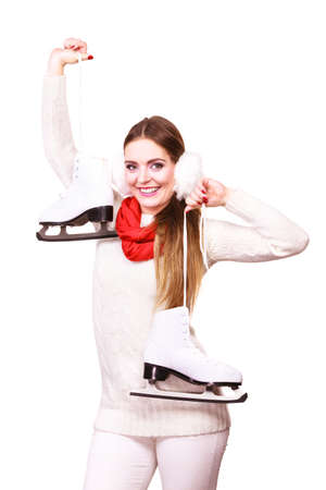 sports clothing: Winter clothing and sport equipment concept. Woman with earmuffs and ice skates. Young lady wearing white outfit. Stock Photo
