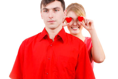 unrequited love: Couple. Serious boyfriend and his crazy playful girlfriend holding red hearts over eyes. Valentines day or unrequited love concept. Stock Photo
