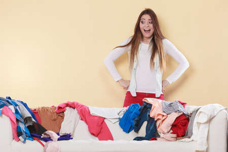 messy clothes: Desperate helpless freaking out woman standing behind sofa couch in messy living room. Young girl surrounded by many stack of clothes. Disorder and mess at home.