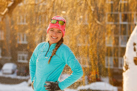 fun in the sun: Girl standing in falling snow. Teen playing in winter park. Health nature fitness fashion relax concept.