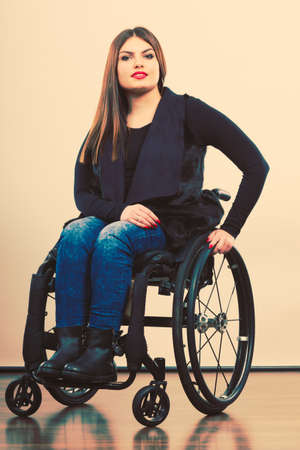 Disability and handicap concept. Young teen handicapped girl sitting on wheelchair. Paralysis and impairment in real life.