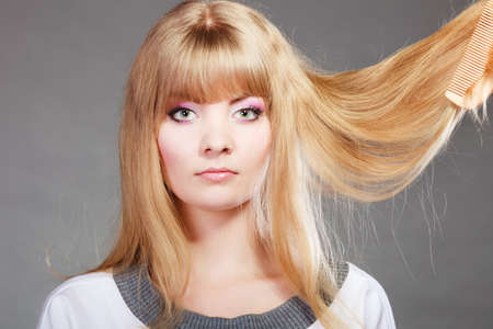 damaged: Haircare. Blonde woman with her damaged dry hair serious face expression gray background Stock Photo