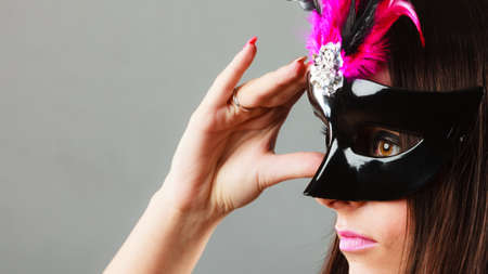 Holidays, people and celebration concept. Closeup woman face profile with carnival venetian mask on gray background. Stock Photo