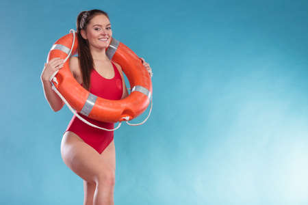 Lifeguard woman girl with ring buoy lifebuoy supervising. Stock Photo