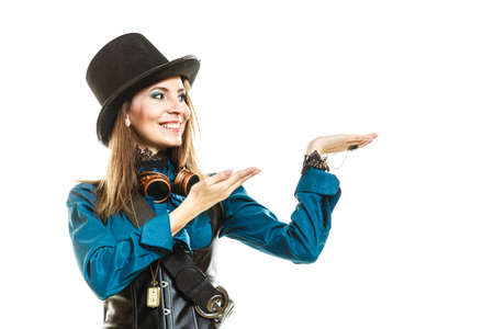 Smiling young steampunk islolated girl on white wearing fancy hat. Fantasy old fashion wearing stylish topper and goggle with open hands palm.