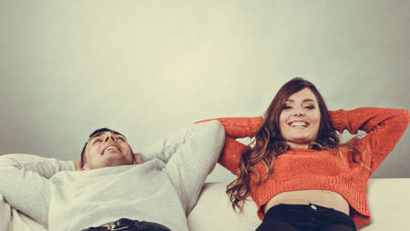 arms behind head: Happy, smiling young couple relaxing on couch at home. Calm, carefree man and woman resting with arms behind head. Healthy relationship. Instagram filtered.