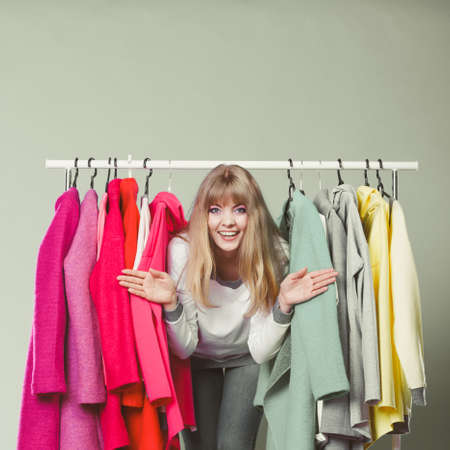 sneaking: Pretty woman sneaking among clothes in wardrobe. Attractive young girl customer shopping in mall shop. Fashion clothing sale concept.
