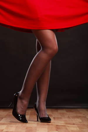 club dress: new year celebration disco concept - woman in evening dress dancing in the club, part of body female legs in black high heels on party floor
