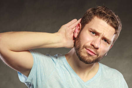 eavesdropping: Gossip man eavesdropping with hand to ear. Guy overhearing listening to rumors. Spying and secret concept. Stock Photo