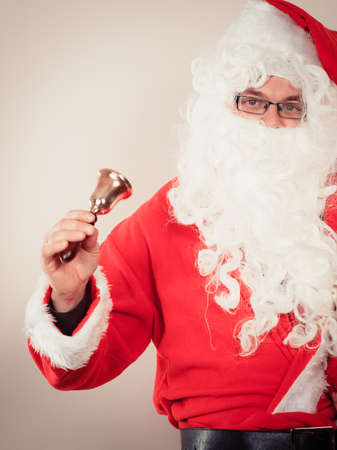 jingle bell: Xmas concept. Santa Claus with jingle bell. Christmas father has long white beard and red outfit.