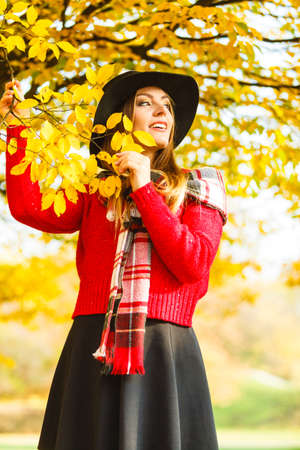 checkered scarf: Autumn season colors in the park concept. Woman standing by the tree. Attractive lady wearing black hat and red sweather and very stylish checkered scarf.