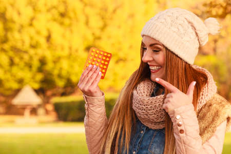 Medication, health concept. Woman with vitamins for autumn. Attractive lady with long hair wearing warm autumnal clothing.