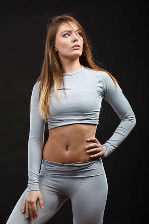 Clothing fashion sport concept. Sporty woman wearing thermoactive underwear. Attractive sporty lady promoting clothes and showing her slim abdomen. Stock Photo