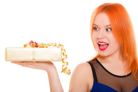 Christmas x-mas winter or valentines day, birthday concept - red hair wide eyed girl holding golden gift box studio shot isolated Stock Photo