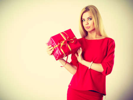Occasions gifts people concept. Beautiful woman with red gift. Young blonde lady wearing nice outfit, dress. Present has the same colour.
