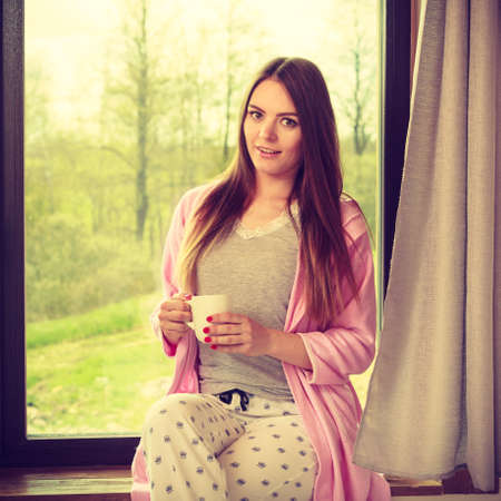 People mornings concept. Beautiful woman drinking morning coffee. Attractive young lady chilling out. Stock Photo