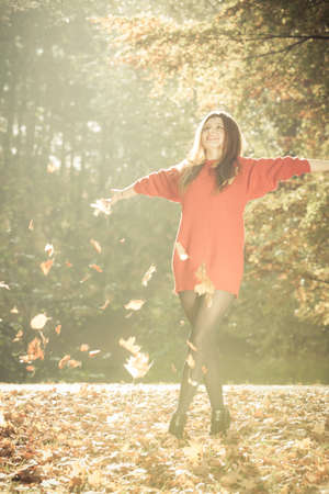enjoyable: Joy and freedom. Young enjoyable attractive woman having fun with autumnal leaves float in the air in park. Playful girl relaxing outdoor.