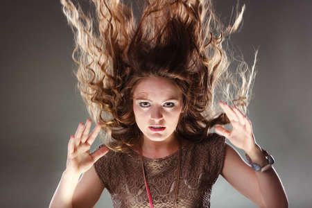 flying hair: Portrait of mysterious enigmatic woman. Young intriguing attractive girl with flying hair in motion. Shining light. Stock Photo