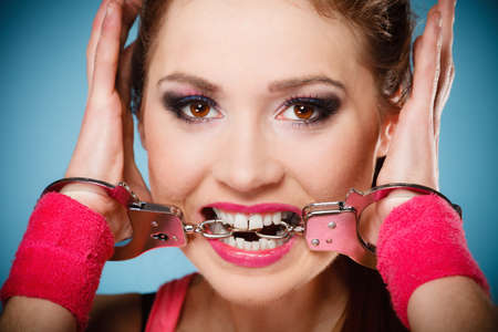 delincuencia: Teen crime, arrest and jail - Criminal teenager girl prisoner woman in handcuffs blue background