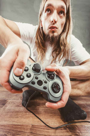 playstation: Lifestyle of young people. Student man spending time on playing games videogames console playstation. Long haired guy focus on gaming.