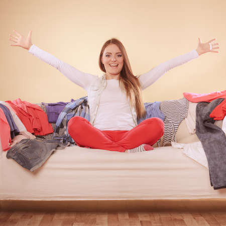 disorganized: Happy woman sitting on sofa couch in messy living room. Young girl surrounded by many stack of clothes. Disorder and mess at home.