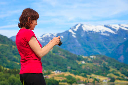 jostedalsbreen: Tourism vacation and travel. Woman tourist taking photo with camera, enjoying mountains fjords view in Jostedalsbreen National Park, Oppstryn (Stryn), Sogn og Fjordane county. Norway Scandinavia.