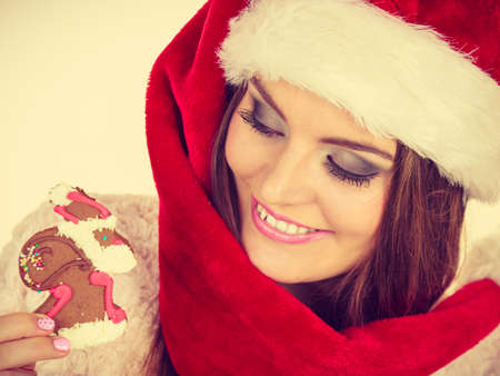 62759362 - Mujer que lleva el sombrero rojo que sostiene la galleta dulce  deliciosa de Navidad del pan de jengibre pequeño Papá Noel. 63c4b2a45ea