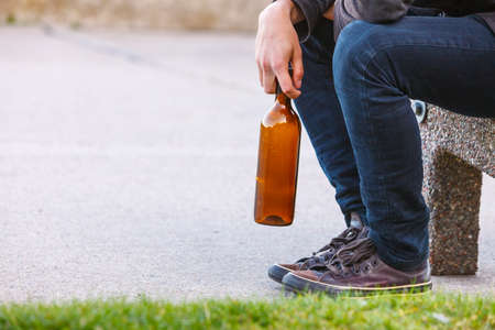 Man depressed with wine bottle sitting on bench outdoor. People abuse and alcoholism problems.
