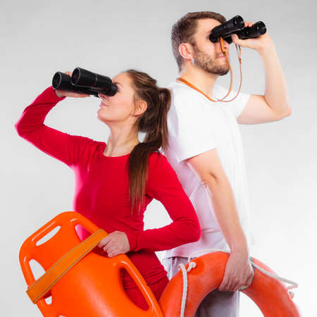 Accident prevention and water rescue. Young man and woman lifeguards on duty looking through binoculars keeping buoy lifesaver equipment on gray Stock Photo