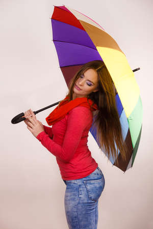 forecasting: Woman fashionable rainy girl in red clothing standing under colorful umbrella. Meteorology, forecasting and weather season concept