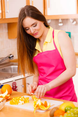 juicing: Woman young housewife in kitchen at home slicing fresh orange fruits on cutting board for salad or juicing. Healthy eating, cooking, raw food, dieting and people concept