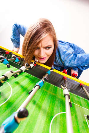 Play and fun concept. Young woman girl having fun with table soccer game. Girl playing spending free time on recreation. Stock Photo