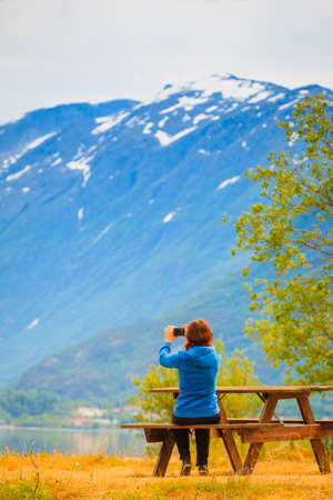 jostedalsbreen: Tourism and travel. Woman tourist taking photo with camera, enjoying mountains lake Oppstrynsvatnet view in Jostedalsbreen National Park, Oppstryn (Stryn), Sogn og Fjordane county. Norway Scandinavia.