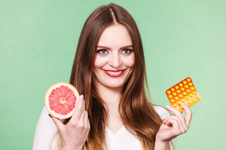 another way: Woman holding pills blister pack vitamin c in one hand and grapefruit in another. Choice between natural and synthetic way of health care. Alternative medicine. Studio shot on green background
