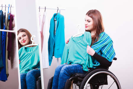 cope: Real people, disability and handicap concept. Teen girl handicapped woman sitting on wheelchair choosing clothes in wardrobe or looking for some clothes in shop