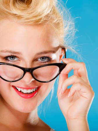 oculista: Optometrista, oculista y el concepto oftalmólogo. Joven rubia retro pin up mujer sonriente con gafas en el fondo azul en el estudio.