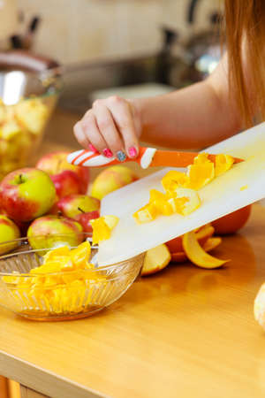 juicing: Woman young housewife in kitchen at home slicing fresh orange fruits on cutting board for salad or juicing. Healthy eating, cooking, raw food, dieting and people concept.